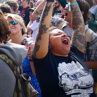 A girl in a festival crowd with their eyes closed and their arms in the air, singing along to the music