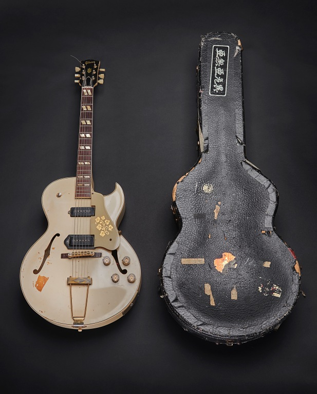 A 1950's Gibson ES-295 with a white finish inside a hardshell contour case with orange plush lining; the guitar was used by Mick Jones during recording of the London Calling album and in the music video for the title track of the album, released as a single in December 1979 © The Clash