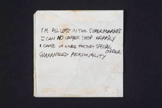 A lyric fragment in Joe Strummer's handwriting for the song Lost in the Supermarket, the 4 lines in black ink on the reverse of an Ernie Ball custom gauge strings paper envelope, the lyrics representing the chorus of the song © Casbah Productions Ltd