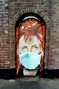 Street art head and shoulders image of Bowie (Ziggy Stardust era) wearing a blue surgical face mask