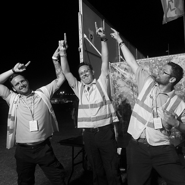 Three security guards dancing at a festival