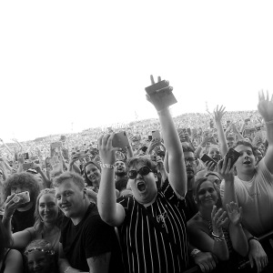 Crowd shot from the front at a festival, lots of people have their mobile phones in the air