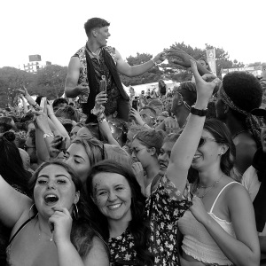 Festival crowd with their hands in the air, one person sitting on their friend's shoulders