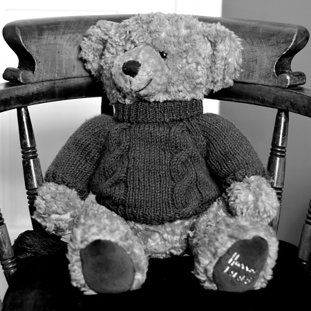 Black and whit shot of a traditional style curly teddy bear wearing a cable knit jumper