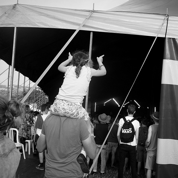 A man with a young girl on his shoulders watching a band from the back of a festival tent