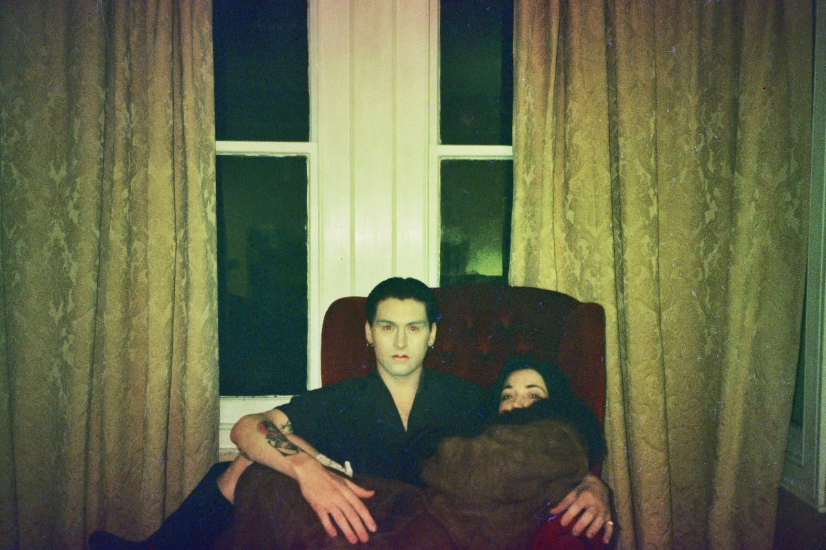 Will and Ellie who make up the band Robbie and Mona, sitting on a red armchair in front of a large window with heavy curtains