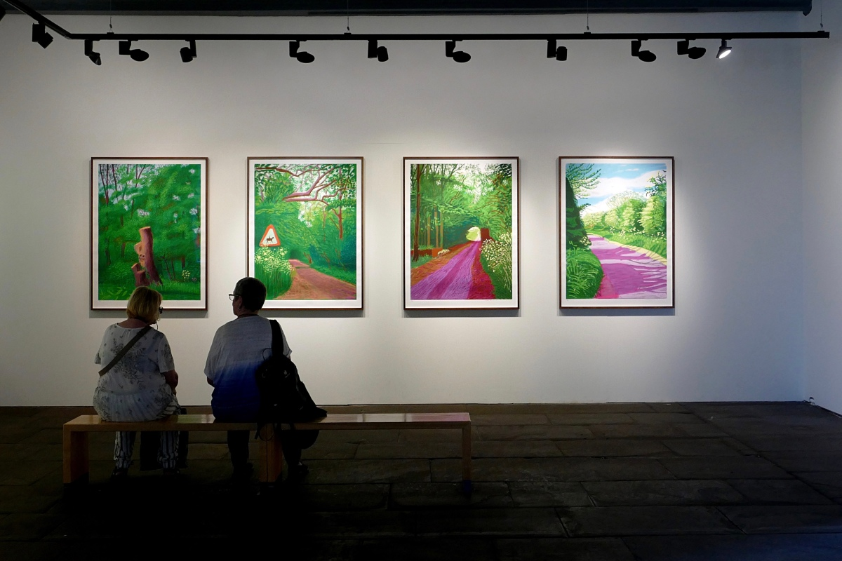 The silhouettes of the backs of two ladies sitting on a bench in an art gallery looking at 4 brightly coloured David Hockney pictures