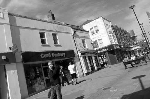 Black & white shot of a fairly empty high street in lockdown, closed shops, 2 people in the distance sitting on a bench, 2 more walking away talking, 1 person at the front of the picture wearing a face mask and talking on their mobile phone