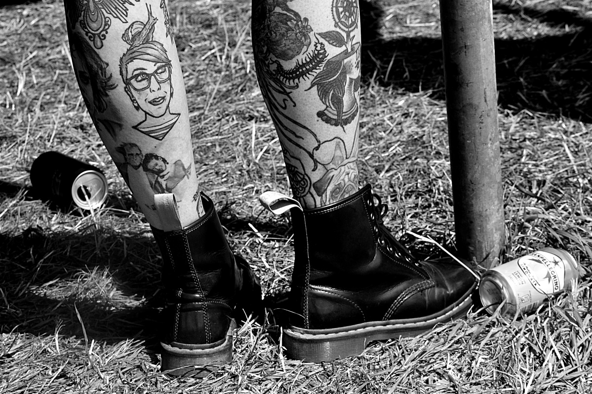 Someone with heavily tattooed legs wearing DM boots, shot from the shins down