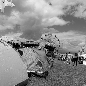 Festival campsite with tents in the foreground and a big wheel in the background