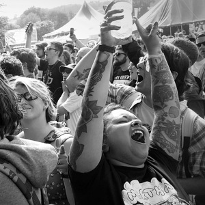 Festival crowd shot, girl at the front has her arms in the air and is singing along to the music