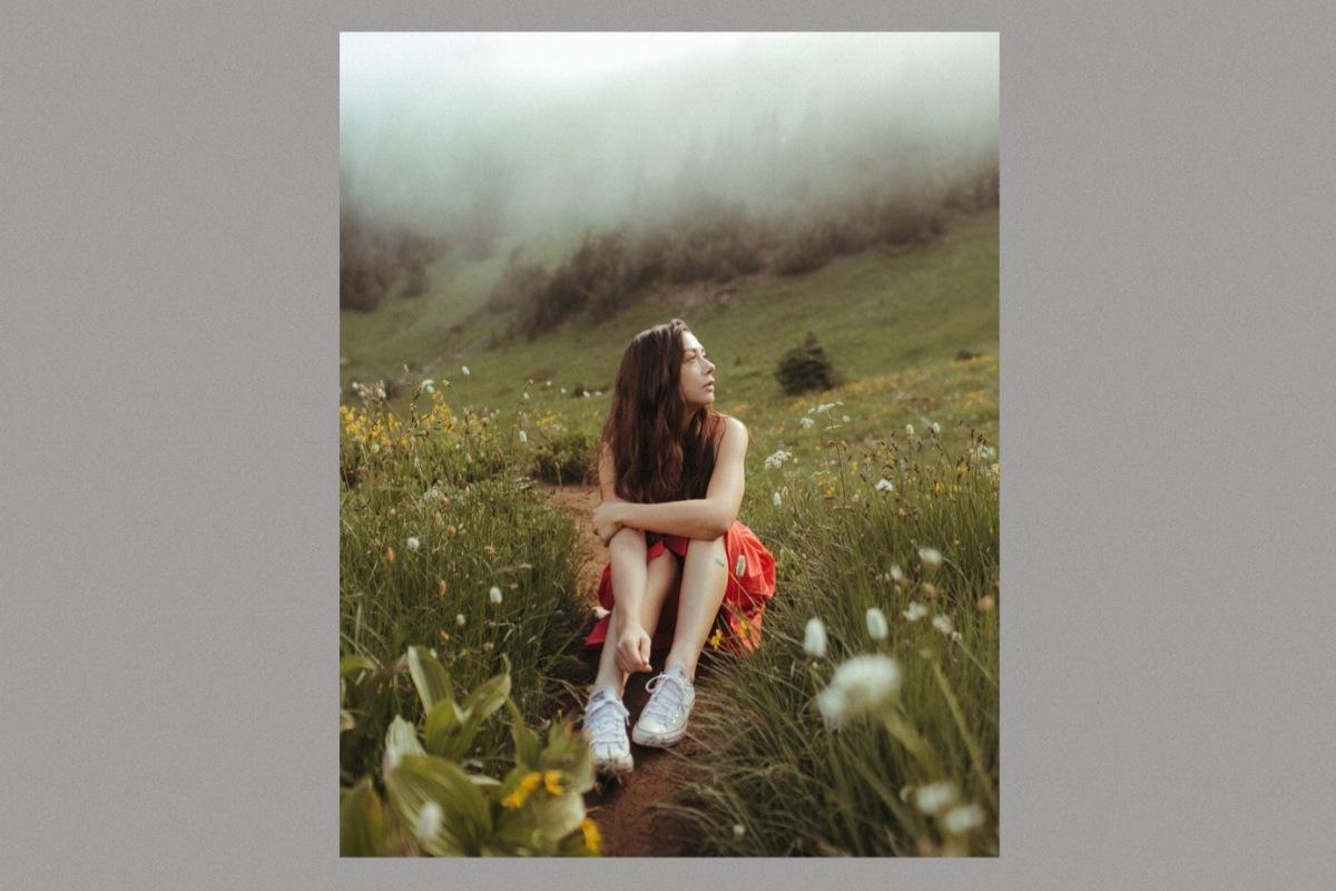 Danielle Durack wearing a red dress sitting in a field