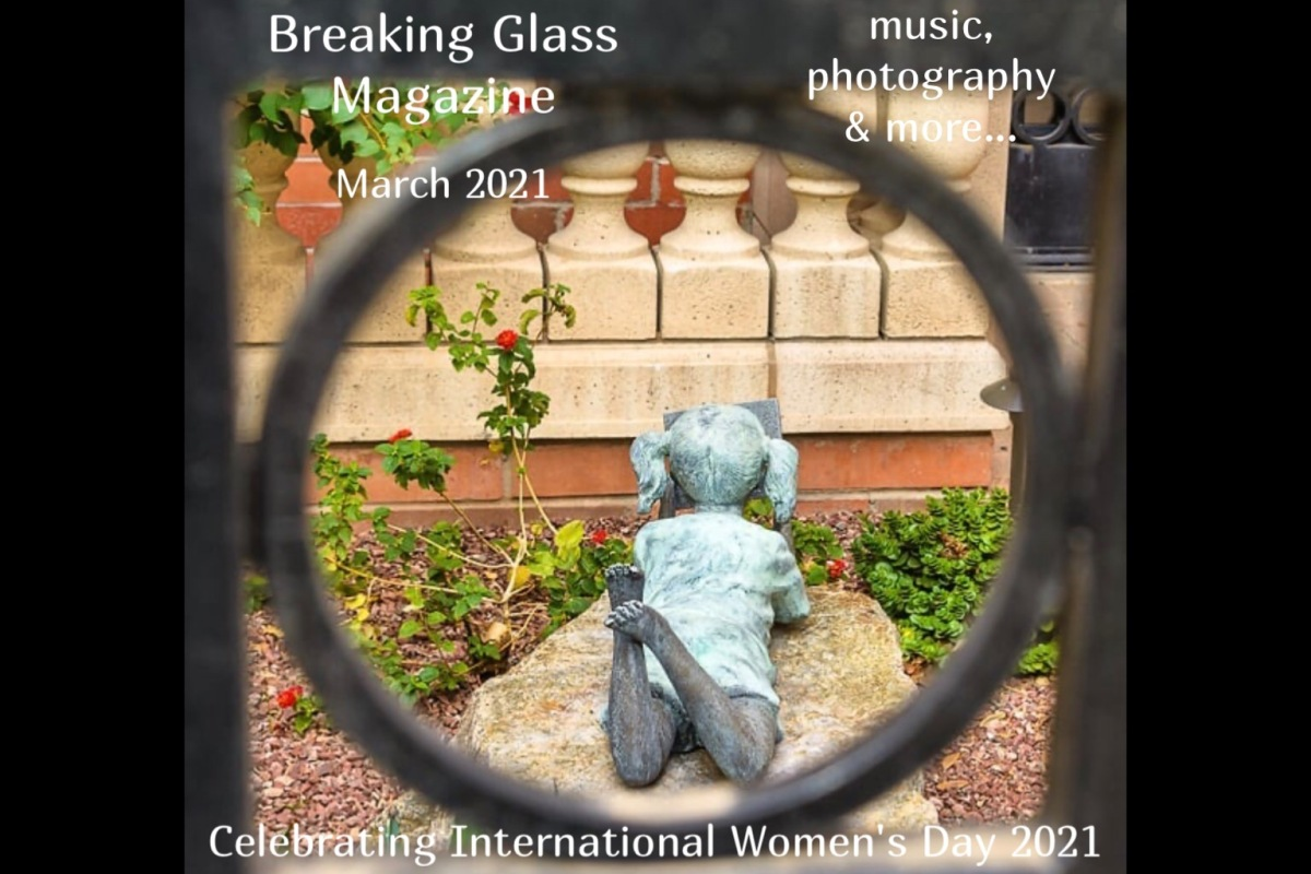 A statue of a girl lying on her stomach reading a book, taken through an iron gate, cover shot for Breaking Glass Magazine March 2021