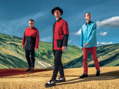 Maxïmo Park standing at the top of a hill all dressed in different colour blocks of red, black and blue